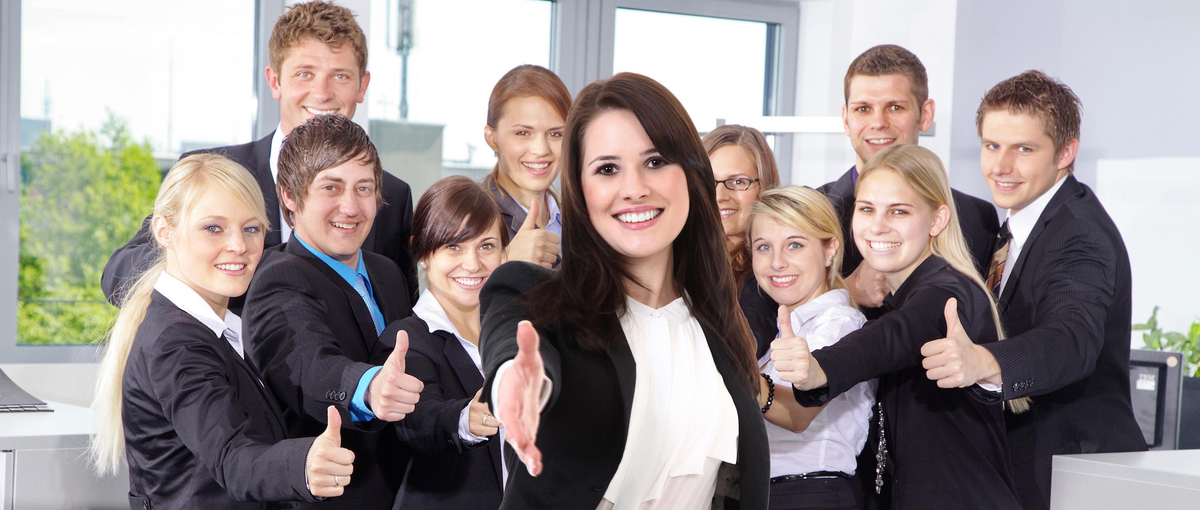 Junge Geschäftsfrau begrüßt freundlich mit Team im Rücke